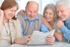 老人读了报纸在桌上 免版税图库摄影
