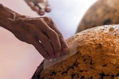 老人黏贴在菩萨雕象的金黄叶子 库存图片