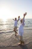 老人&妇女在海滩的夫妇日落 库存照片