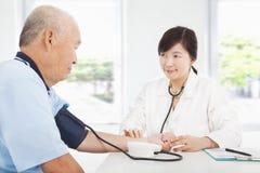 老人医生测量的血压  免版税图库摄影