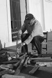 老人崩裂一些木头 免版税库存照片