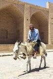 老人驴骑马在Kharanagh村庄,伊朗 免版税图库摄影