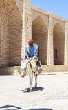 老人驴骑马在Kharanagh村庄,伊朗 免版税库存图片