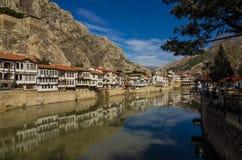 老传统无背长椅房子河场面在阿马西亚,土耳其阿马西亚是一个城市在北土耳其并且是阿马西亚的首都 免版税库存照片