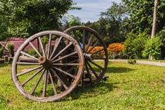 老作为装饰的堡垒虚张声势无盖货车木轮子在庭院 免版税库存图片