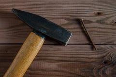 老使用的锤子、木把柄、金属头和生锈的钉子在木背景 免版税库存照片