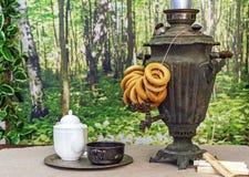 老俄国俄国式茶炊用在一张木桌上的百吉卷 免版税库存图片