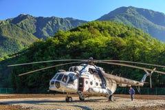 老俄国直升机MI-8在着陆架站立在绿色高加索山脉森林里并且为飞行准备 免版税库存照片