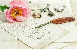 老信件、桃红色牡丹花和古董用羽毛装饰笔 葡萄酒 库存图片