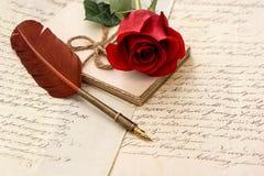 老信件、玫瑰色花和古董用羽毛装饰笔 免版税库存照片