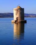 老倾斜的风车在水,奥尔贝泰洛,意大利中 库存图片