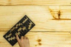 老做在木头的算盘和手 库存照片