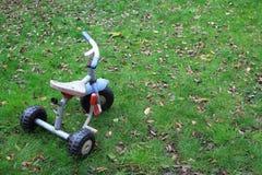 老儿童三轮车三轮子在庭院里骑自行车 免版税库存图片
