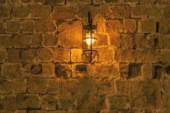 老光在垂悬在中世纪街道堡垒墙壁上的晚上 库存图片