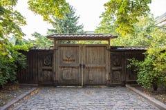 老入口门由与石头或摊铺机路的木头制成  免版税库存照片