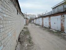 老具体车库典型的复合体与闭合的金属门的在俄罗斯 车道路通过车库与 免版税库存图片