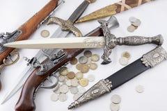 老军事匕首、枪和硬币 库存照片