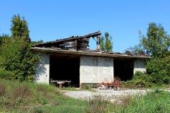 老农业农场设备以部分地生锈的在被放弃的未完成的车库前面的干草特纳和无盖货车的形式与 免版税库存图片