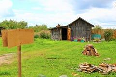 老农村木房子在俄国村庄在夏天晴天 标志 免版税库存图片