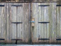 老农村灰色与螺栓紧固和生锈的铁铰链的板条木板条门 图库摄影