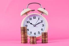 老减速火箭的时钟和硬币在桃红色背景 库存图片