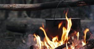老减速火箭的汤准备的阵营平底深锅煮沸的水在森林火焰火篝火的火夏天晚上 股票视频