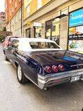 老减速火箭的经典汽车雪佛兰因帕拉在城市街道上的SS后面看法1965年 汽车详述 库存图片