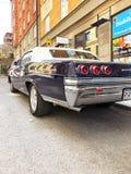 老减速火箭的经典汽车雪佛兰因帕拉在城市街道上的SS后面看法1965年 汽车详述 免版税库存图片