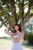 年轻老化妇女与一棵树的反射复活的 免版税图库摄影