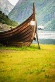 老北欧海盗小船和渡轮在挪威海湾 库存图片