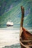 老北欧海盗小船和渡轮在挪威海湾 图库摄影