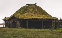 老北欧海盗村庄在有有雾的小山的冰岛 在草盖的老木大厦 免版税库存照片