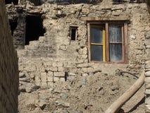 老半被破坏的砖房子墙壁、下落的石头的黑开头,与老木制框架的窗口,褐色和 免版税库存照片