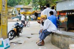 老印地安人坐在街市上并且抽香烟Puttaparthi 2月11日2018年,印度 免版税库存图片