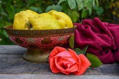 老印地安花瓶用果子和猩红色玫瑰在木桌上 免版税库存照片