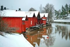 老历史的波尔沃,芬兰 河沿的红颜色葡萄酒木谷仓存贮房子与雪在冬天 免版税库存图片