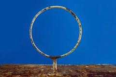 老反对天空蔚蓝的篮球生锈的圆环,底视图 库存图片