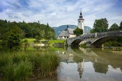 老反映在河, Bohinj湖,斯洛文尼亚的教会和桥梁 免版税库存图片