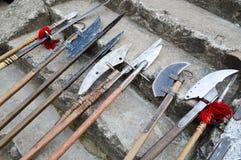 老古老中世纪冷的武器,轴,olibards,刀子,有木把柄的剑在城堡的石步舔 免版税库存照片