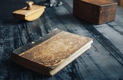 老古色古香的书和其他对象在黑木桌上 库存图片
