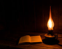老古色古香的书打开了与灼烧的煤油灯 图库摄影