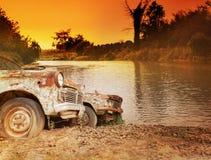 老古色古香的车汽车parkat河沿在微明下 免版税图库摄影
