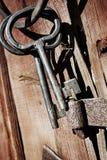 老古色古香的钥匙和圆环反对木头 免版税库存图片