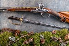 老古色古香的长的枪和老军刀有森林静物画的在灰色背景,历史武器 免版税库存图片