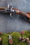 老古色古香的长的枪细节有森林静物画的在灰色背景,历史武器 免版税图库摄影
