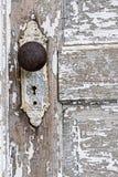 老古色古香的门把手和发隆隆声的白色油漆背景 免版税库存照片