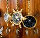 老古铜色指南针在木墙壁上的一个链子垂悬 库存照片