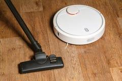 老吸尘器和新的机器人吸尘器在地板上 免版税库存图片