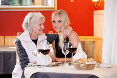 老和少妇在食用的表上快餐 免版税库存照片