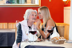 老和少妇谈话在餐馆表上 免版税库存图片
